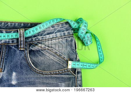 Close Up Of Jeans With Measure Tape Around Waist