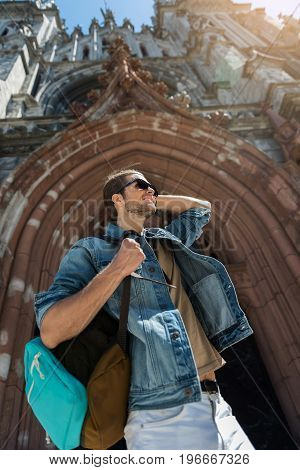 Portrait of jolly young bearded man standing near arch entrance to huge medieval castle. He is wearing sunglasses, smiling and carrying backpack. Low angle