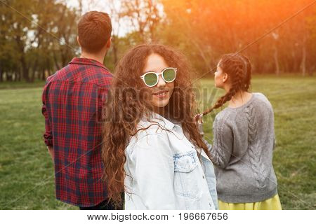 Curly haired girl in sunglasses wearing jacket standing in park with friends looking at camera.