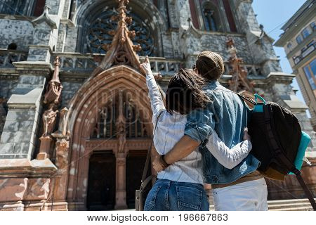 Low angle of young couple standing in front of huge gothic building. They are hugging each other and girl is pointing at construction. Copy space in left side. Focus on back