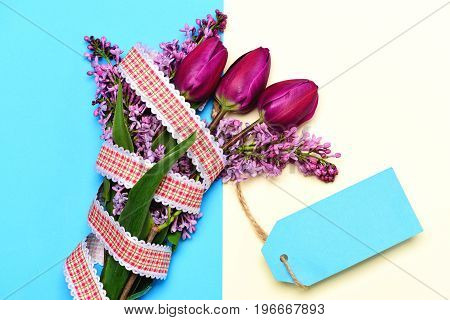 Cyan blue label for notes tied to bunch of spring tulips and lilac tree flowers on turquoise and light beige background top view. Present for womens day
