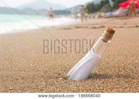 Message in a glass bottle on the beach. People bathe in the sea on the waves. Found a note on salvation please help
