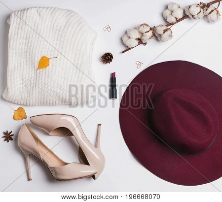Autumn stylish woman's outfit. Sweater, hat, shoes and small autumn related items, top view.