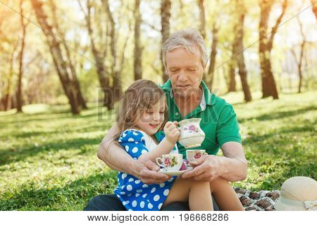 Tea picnic in the park for grandfather and his granddaughter on sunny summer day.