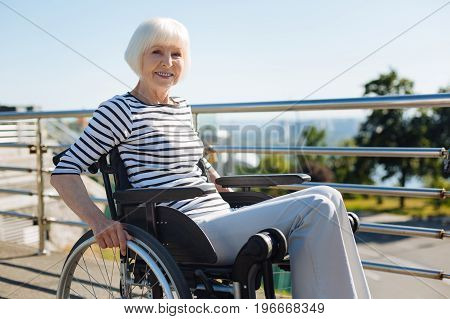 Fun at any age. Energetic strong aged lady rolling like a pro while taking a daily walk and enjoying the warm weather outdoors