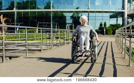 Active in every way. Stunning determined pretty lady sitting in a wheelchair leading an active life and enjoying the warm weather outdoors
