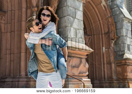 Portrait of happy young lady and guystanding and laughing beside old gothic style building. She is hugging tight her boyfriend and sitting on his back. Copy space in right side