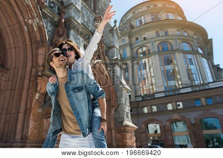 Portrait of happy young lady sitting on back of her bearded boyfriend. They are standing near old gothic style and up-to-date buildings and smiling. Low angle. Copy space in right side