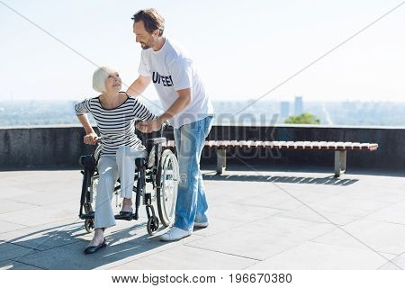 Take a step. Charming motivated nice man taking senior woman for a walk and helping her standing up while she looking rather determined