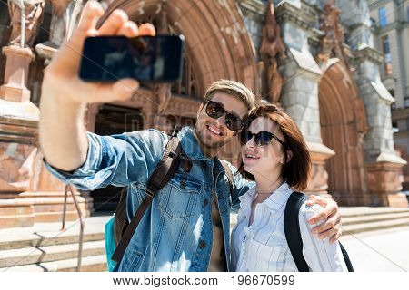 Waist up portrait of jolly young man with beard and woman. They are taking selfie picture via mobile phone in background of medieval gothic building. Guy is hugging lady with smile