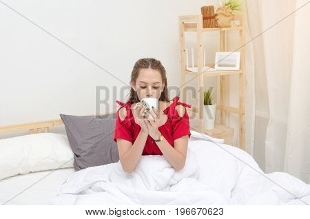 young asian woman beautiful smile in red pajamas with coffee cup on bed waking up at the morning in bedroom with sunlight effect selective focus soft focus good morning holiday lifestyle concept