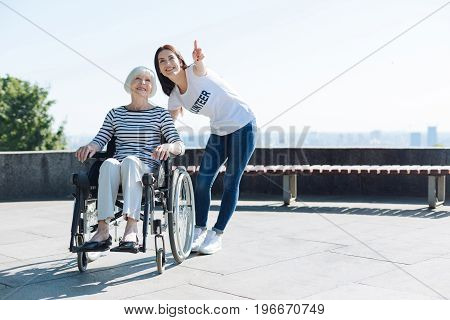 There it is. Attractive energetic pretty girl helping elderly lady and enjoying the beauty of the nature together while taking a daily walk in the park