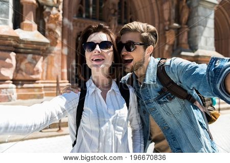 Waist up portrait of happy young couple in sunglasses standing close back to old building. They are hugging, laughing and taking photo of themselves
