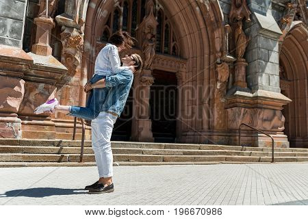 Happy young man is lifting and holding his girlfriend near old medieval building. She is embracing him by neck and they are smiling to each other. Copy space in right side