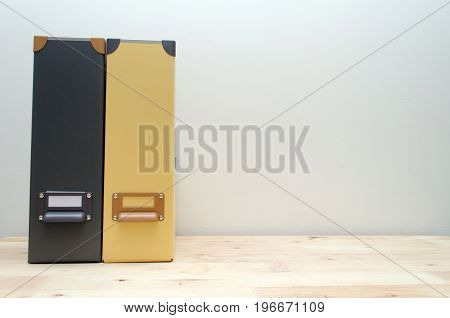 black and yellow office document file folders stack on wooden desk with white wall background business concept