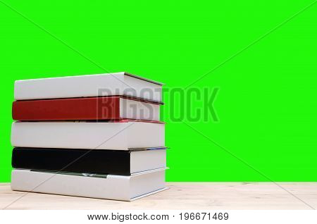stack book on desk no labels blank spine with green background education back to school and business concept copy space