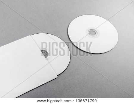 Blank compact disk on gray paper background. CD with envelope. Template for branding identity.