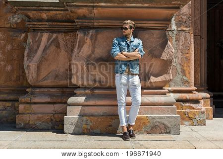 Full length portrait of pensive young bearded guy in sunglasses standing by ancient building. He is leaning on uneven wall and looking aside. Copy space in left side