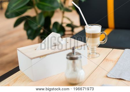 Close Up View Of Coffee Latte, Sugar And Napkins On Table In Cafe