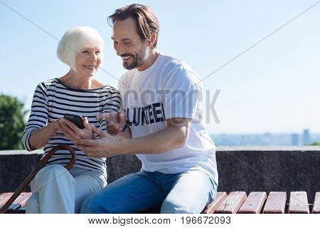 I used to be a pretty one. Delicate witty aged woman feeling talkative and sharing her personal photos with the volunteer who taking her for a daily walk