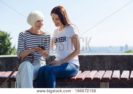And this is me back in time. Talkative bright aged lady enjoying warm day outdoors and communicating with the volunteer who escorting her for a daily promenade