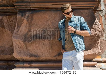 Portrait of sad youthful bearded guy in sunglasses leaning on uneven old building wall. Copy space in left side