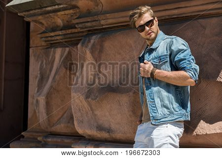 Portrait of upset young bearded man in sunglasses standing close to uneven wall of old architecture. Copy space in left side