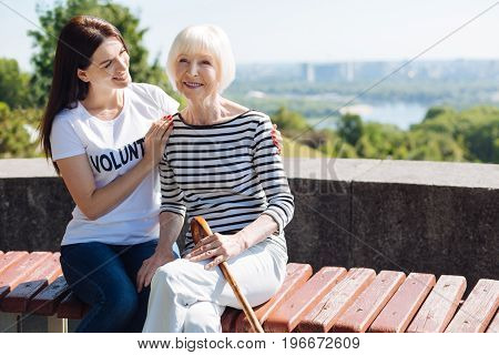 Not alone anymore. Dreamy elegant aged woman feeling thankful while young lady who working as a volunteer keeping her company