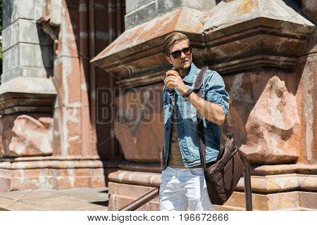 Portrait of serious young bearded guy standing near big old building and drinking coffee. He is wearing sunglasses and carrying laptop bag on shoulder. Copy space in left side