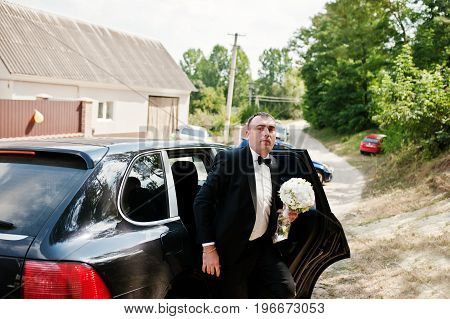 Handsome Groom Walking Out Of The Cool Decorated Wedding Suv With A Bouquet In His Hands.