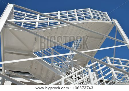 White, metal, spiral staircase to the blue sky - stairways to haven