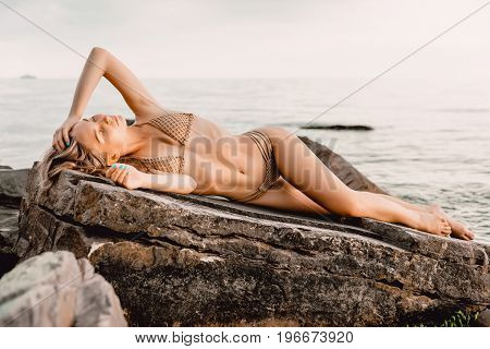Young sexy woman in bikini swimsuit relaxed on stone, tropical island, summer vacation