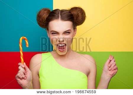 Young model with two buns looking at camera and shouting with candy stick in hands.
