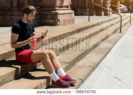 Pensive young bearded man in sportswear is sitting on long stone stairs on street and looking at his mobile. He is using earphones and holding bottle of water. Copy space in right side