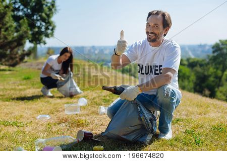 Saving the nature. Clever handsome gallant guy being enthusiastic about the environment while gathering garbage on a lawn while working pro bono for sake of local community