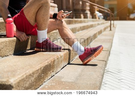 Close up of legs of young athlete sitting on street stairs. He is holding mobile phone and typing something. Bottle of water standing beside