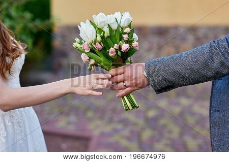 Groom gives the bride a wedding bouquet of flowers.