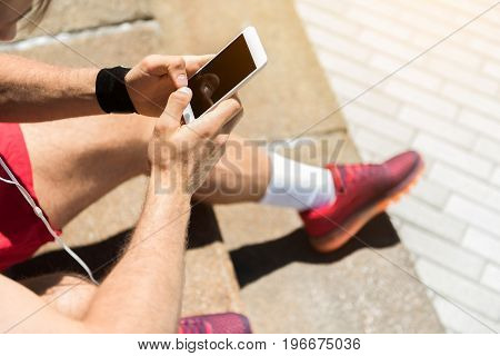 Close up of hands and legs of young sportsman sitting on steps outdoor and holding cellphone. He is typing something and using earphones. Top view