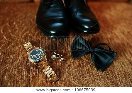 Groom's Wedding Black Shoes, Golden Watch, Bow Tie And Cufflinks On The Ground.