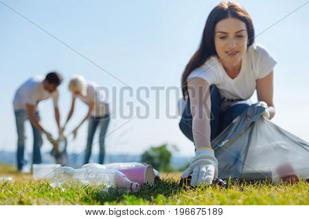 Pro bono services. Motivated optimistic active lady participating in eco campaign as a volunteer and collecting garbage on the lawn in the local park