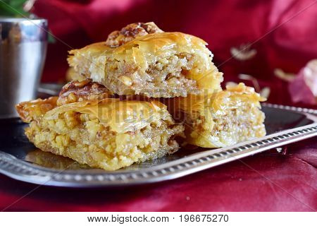 Traditional Greek baklava made with filo dough, sugar syrup and wallnuts on a metal tray with metal coffee cup on a purple cloth background