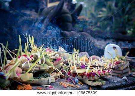 Traditional balinese offerings to gods in Bali with flowers and aromatic sticks. Bali.