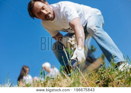 Bad decisions for nature. Persistent productive motivated guy working as a volunteer while participating in eco campaign and gathering garbage in local park