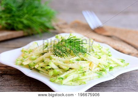 Fresh courgette salad with cheese, sesame and dill on a white plate. Raw courgette recipe. Vintage style