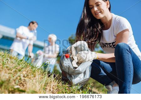 Time for good cause. Unconventional smart admirable lady gathering rubbish on a lawn while participating in eco initiative and working as a volunteer