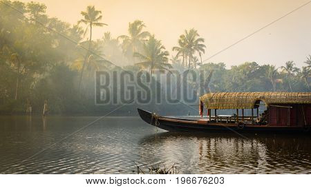 A traditional house boat is anchored on the shores of a fishing lake in Kerala's Backwaters India.
