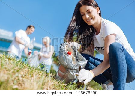 Enthusiastic scavenger. Motivated passionate pretty lady picking up litter while working as a volunteer and participating in eco campaign
