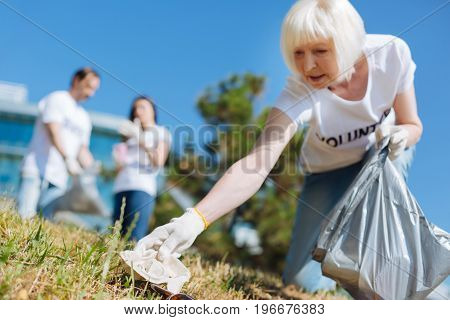Making the difference. Progressive devoted senior woman supporting eco initiative and joining it while helping cleaning local park from garbage