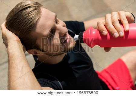 happy young athlete with beard sitting outdoor and drinking water from special sport bottle. He is closing eyes with pleasure. Top view