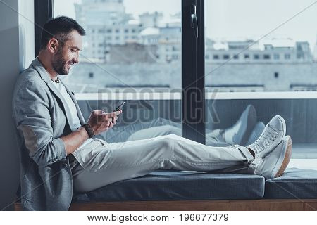 Optimistic news. Cheerful stylish man with stubble is sitting on windowsill, holding mobile phone while texting email and expressing gladness on cityscape background. Copy space in the right side